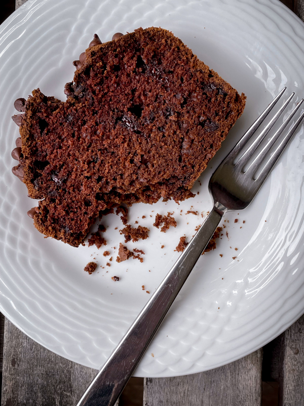 A slice of double chocolate pumpkin bread on a white plate with a fork.